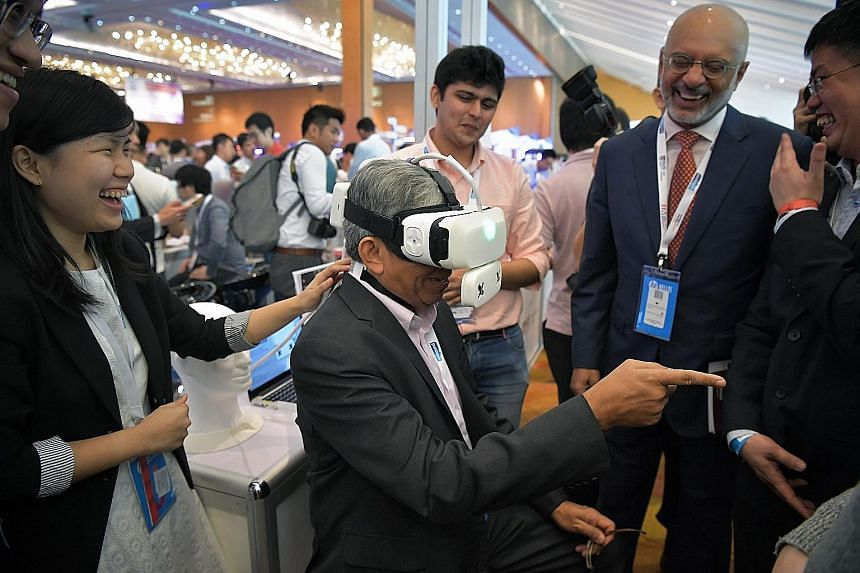 Dr Yaacob Ibrahim trying out the Ambiotherm, a virtual reality headset accessory developed by NUS that simulates ambient temperatures and wind conditions, at the innovation conference yesterday. With him was DBS Group chief executive Piyush Gupta (ri