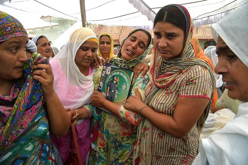 Ms Paramjeet Kaur, the mother of slain Indian Army soldier Paramjeet Singh, crying at his funeral ceremony in Vein Pein village, some 45km from Amritsar on Tuesday. India has accused Pakistan of killing two of its soldiers and mutilating their bodies