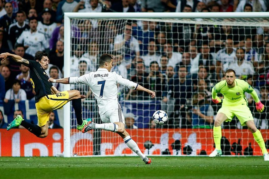 Real Madrid forward Cristiano Ronaldo shoots to score his second goal against Atletico Madrid in the Champions League semi-final first-leg clash at the Bernabeu as Stefan Savic fails to make a vital block.