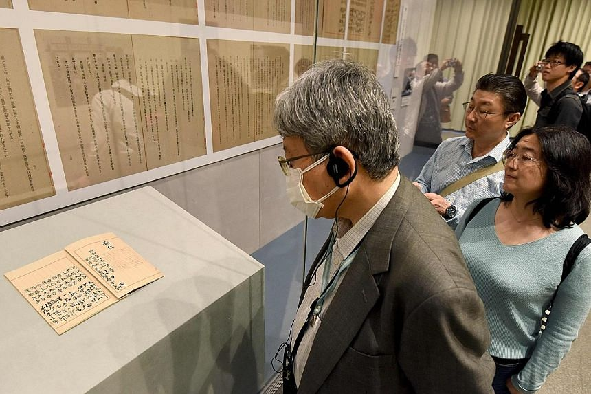 The original Japanese Constitution and its copies on the wall on display on Tuesday at an exhibition at the National Archives of Japan in Tokyo to commemorate the charter's 70th anniversary.