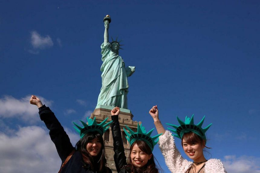 Tourists pose in front of the Statue of Liberty in New York City.