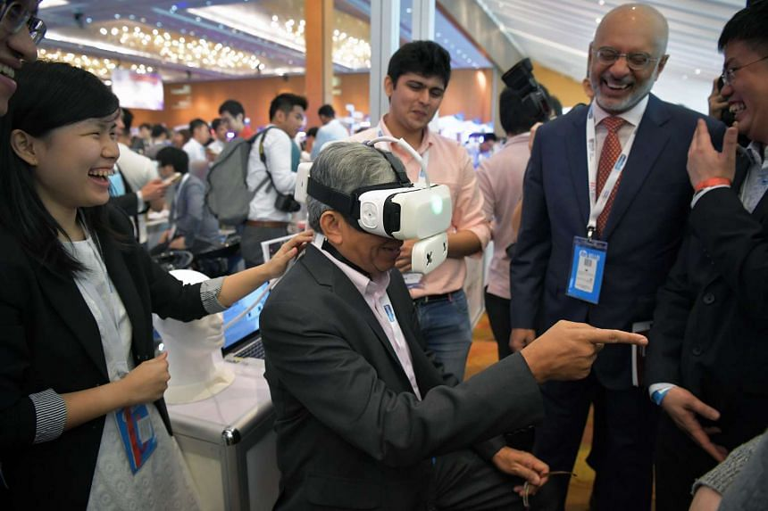 Communications and Information Minister Yaacob Ibrahim  tries out the Ambiotherm, which is an accessory to the virtual reality device which simulates ambient temperatures and wind conditions. DBS CEO Piyush Gupta (to the right of Mr Yaacob)  looks on