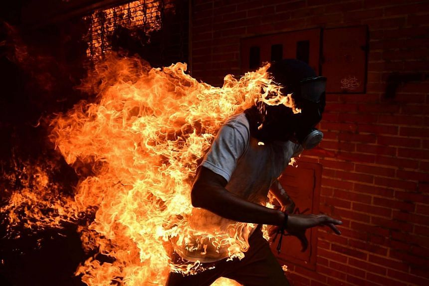 A demonstrator catches fire during clashes with riot police.