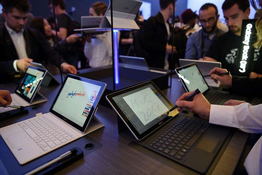 Journalists test the Samsung Galaxy Book after its presentation on Feb 26, 2017 in Barcelona.