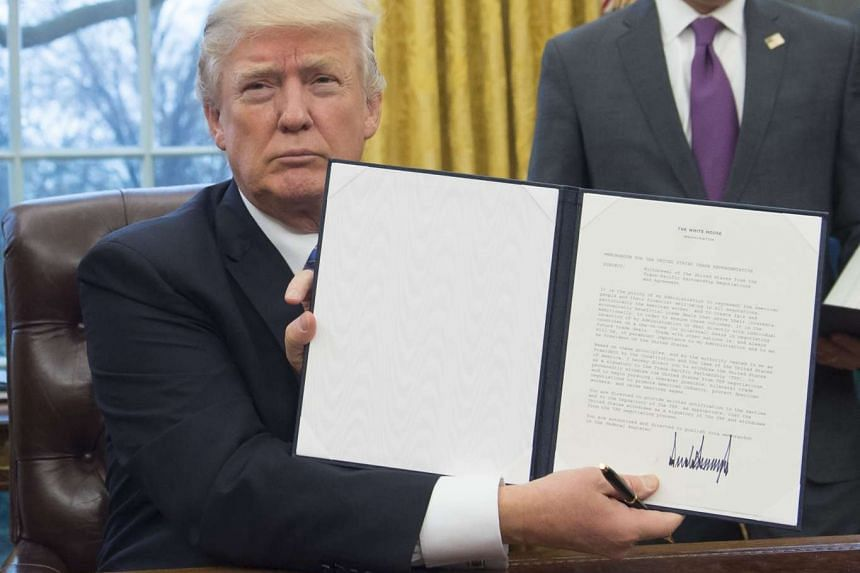 US President Donald Trump holds up an executive order withdrawing the US from the Trans-Pacific Partnership.