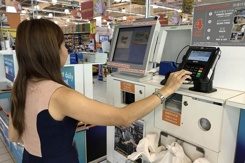 A customer using the unified POS terminal at the self-checkout counter at a Giant supermarket.
