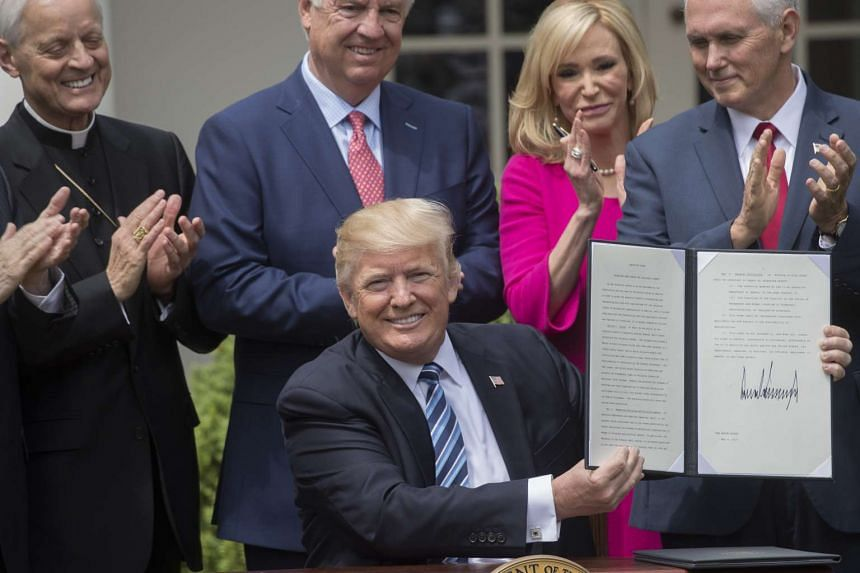 Trump signs an executive order aimed at easing restrictions on political activity by tax-exempt churches and charities.