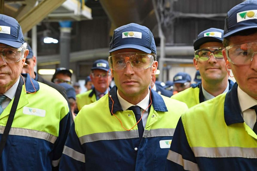 Macron (centre) visits a glass-making company on the campaign trail, May 4, 2017.