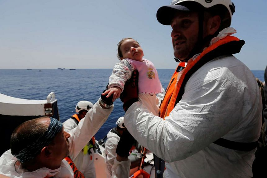 A baby migrant is brought onto the ship during a rescue operation in the central Mediterranean on May 4, 2017.
