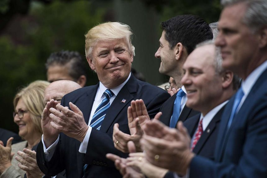 Mr Donald Trump (left) looks at House Speaker Paul Ryan after the House pushed through a healthcare Bill.