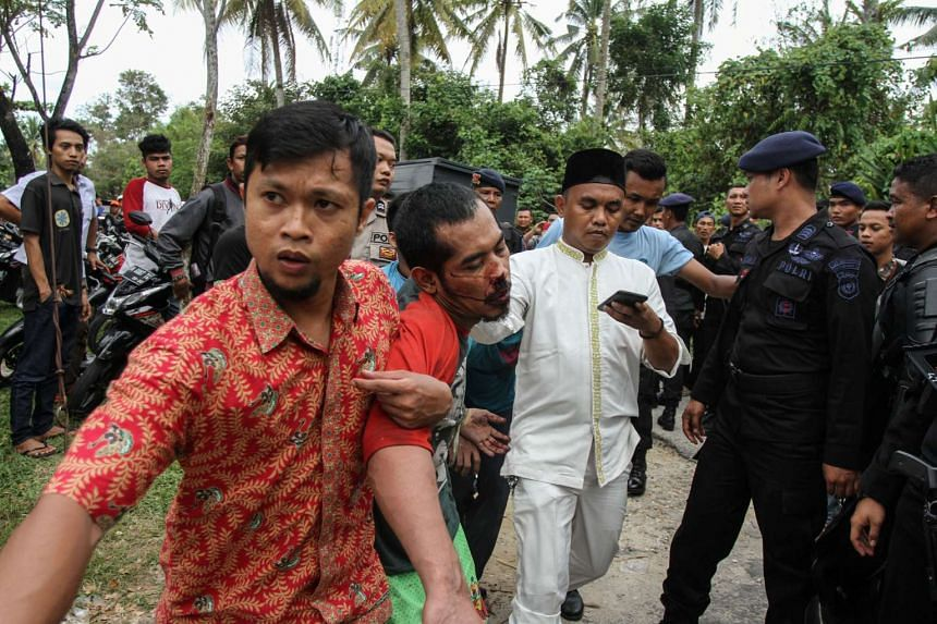 A plainclothes policeman (left) detains a prisoner who escaped from the Sialang Bungkuk jail in Pekanbaru on Indonesia's Sumatra island on May 5, 2017.