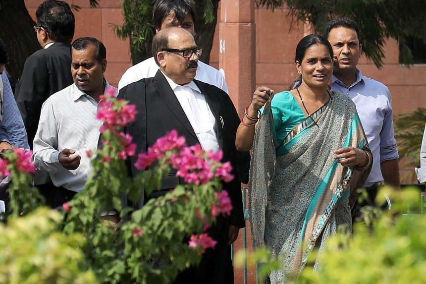 The father and mother of murdered 2012 gang rape victim leave with a lawyer the Supreme Court after the judgment in New Delhi, India, on May 5, 2017.