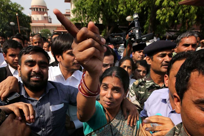 The mother of Indian gang rape victim 'Nirbhaya' walks through a crowd of media representatives as she leaves The Supreme Court in New Delhi on May 5, 2017.