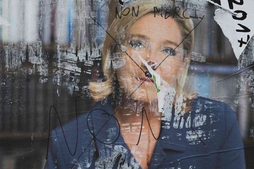 A vandalised campaign poster for far-right presidential candidate Marine Le Pen, May 5, 2017, in Paris.