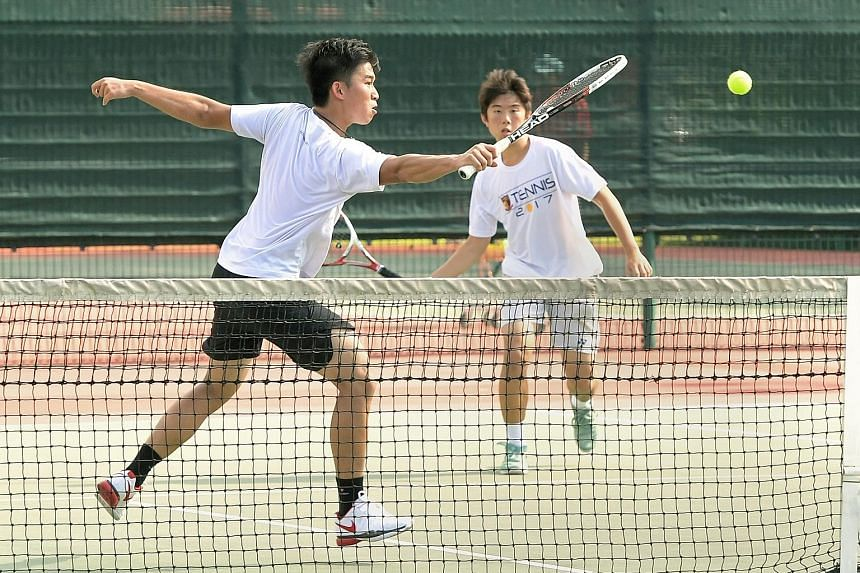 Julian Cheng of Anglo-Chinese School (Independent) hitting a backhand volley as Joshua Tan looks on during the Schools National A Division tennis final. After a tie-breaker decided the first set, the pair went on to beat Ashton Tan and Wesley Wong of
