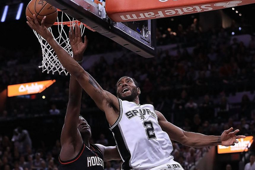 Spurs forward Kawhi Leonard goes up for a reverse layup as Rockets centre Clint Capela attempts to defend during Game Two.