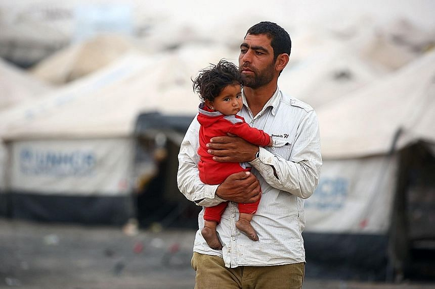 """A displaced Syrian, who fled the countryside surrounding the Islamic State in Iraq and Syria's stronghold of Raqqa, at a temporary camp in the village of Ain Issa on Tuesday. Moscow has been touting a plan to create safe zones in Syria aimed at """"furt"""