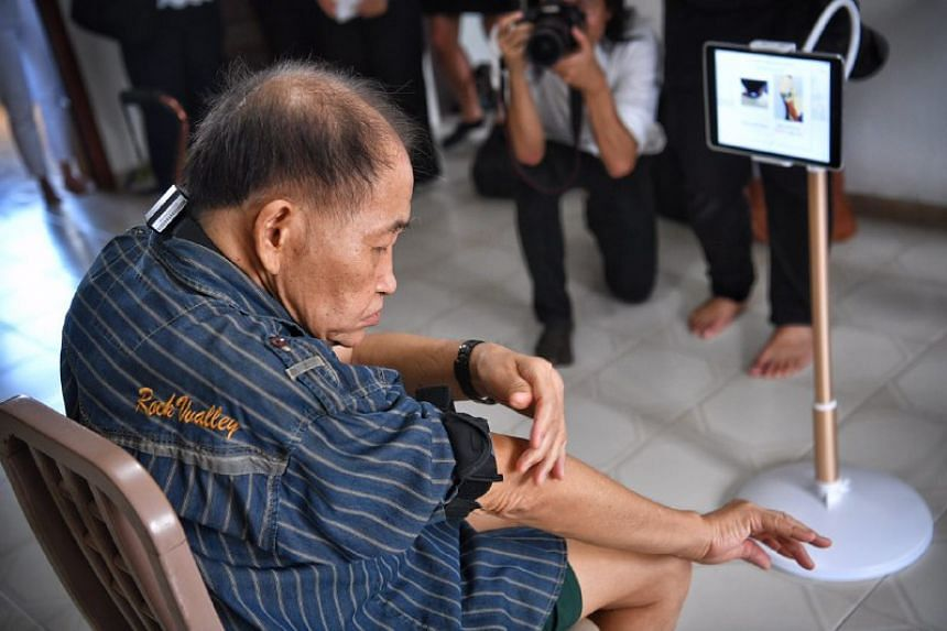 Mr Chin Tian Loke, 72, trying out the Smart Health TeleRehab system.