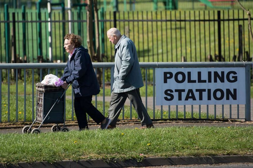 An elderly couple walk past a sign for a polling station in Manchester.