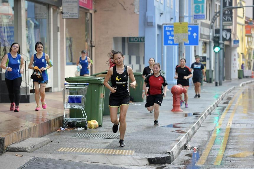 Runners return to the cafe after getting soaked in a sudden downpour during their 3km Breakfast Run on May 6, 2017.