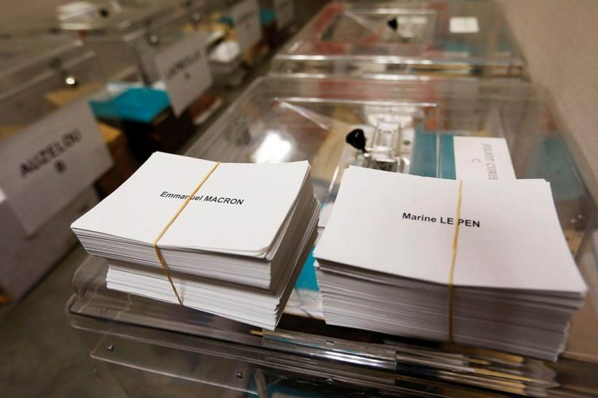Ballots with the names of 2017 French presidential election candidates Emmanuel Macron and Marine Le Pen are seen near ballot boxes at a polling station in Tulle, France, on May 6, 2017.