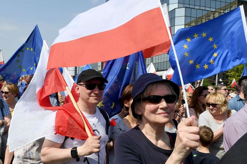 Demonstrators hold Polish and EU flags during the march in Warsaw, May 6, 2017