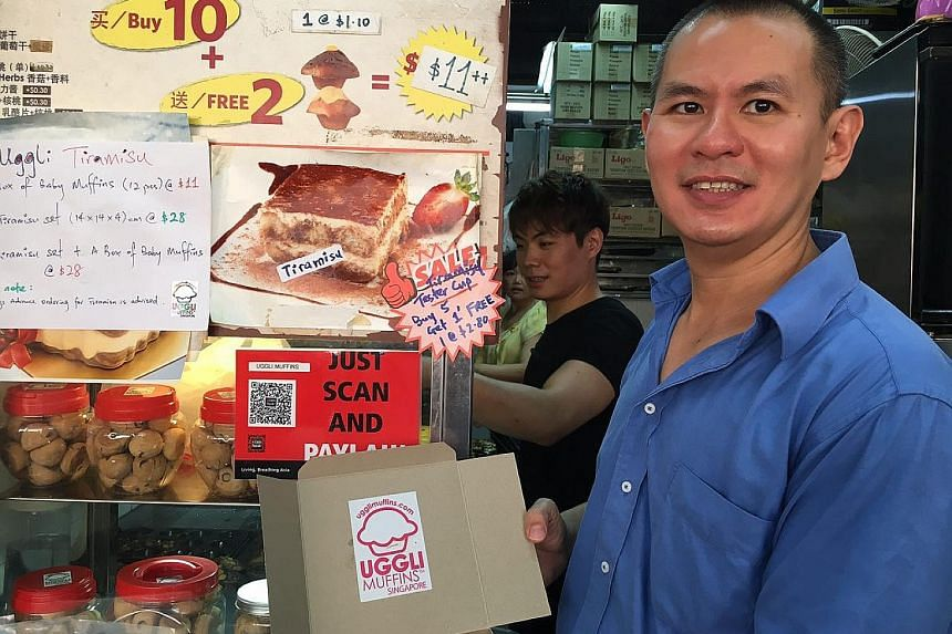 Mr Anton Tan set up the QR-code payment function yesterday at his Uggli Muffins stall in the Toa Payoh West Market and Food Centre. Looking for change can be time-consuming, he says, so he finds it quite useful.