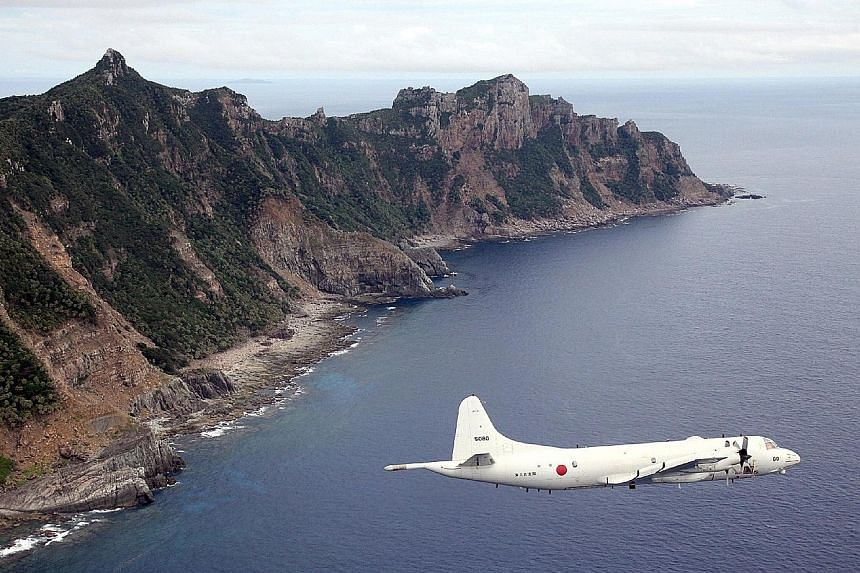 A P-3C patrol aircraft flying over one of the disputed East China Sea islets, known as Senkaku islands in Japan and Diaoyu islands in China. Japan is reportedly donating decommissioned P-3Cs to Malaysia.