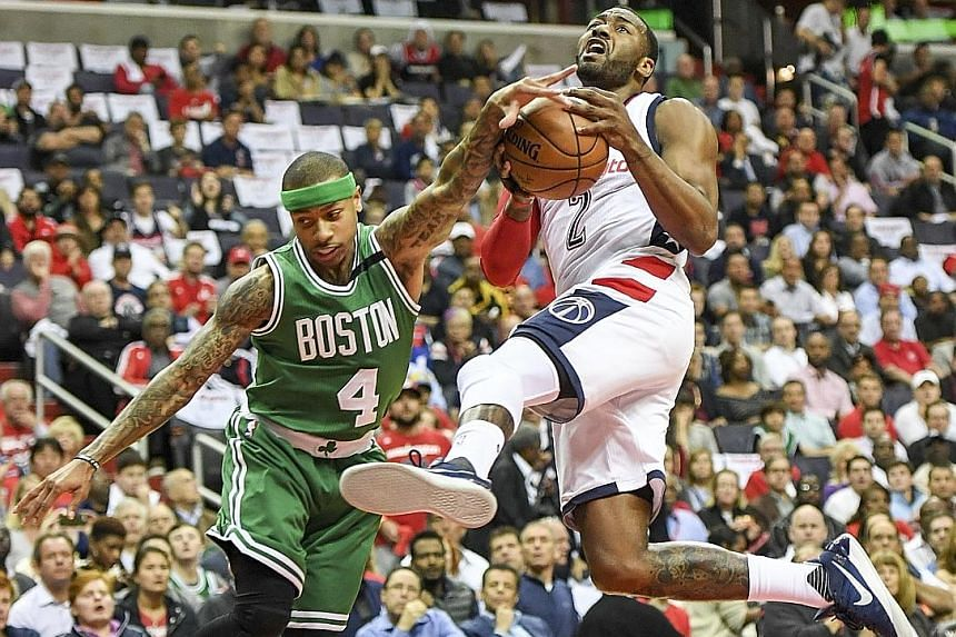 Wizards forward Kelly Oubre Jr (above, left) is held back by referee Monty McCutchen after shoving Celtics centre Kelly Olynyk during the second quarter of their Eastern Conference semi-final clash.