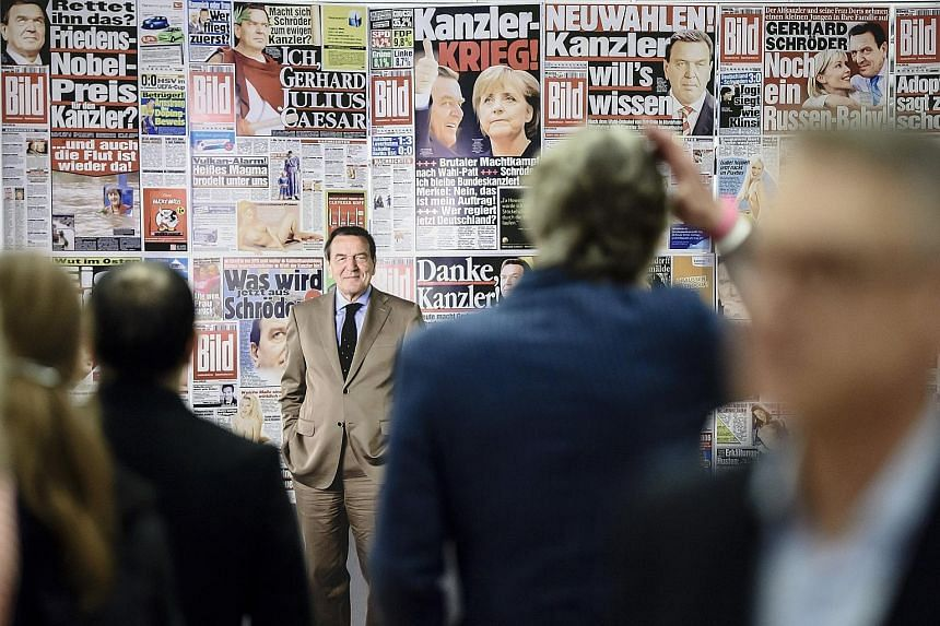 A photograph of former German chancellor Gerhard Schroeder looming large among other news photos from the German tabloid newspaper Bild during the opening of the exhibition Foto.Kunst.Boulevard in the Martin-Gropius-Bau exhibition hall in Berlin on T