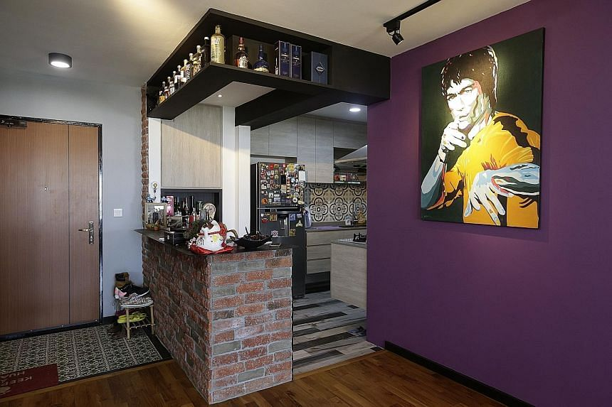 A purple wall with a curvy cutout (above) forms the entrance to the dining room in the home (right) of married couple Leon Luo and Gwen Chiong. A tree-inspired cement feature (above) acts as the backdrop for the television and lights; while a Bruce L