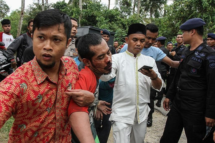 A prisoner being taken back by a plainclothes officer after escaping yesterday from the Sialang Bungkuk jail in Pekanbaru, Riau province, Sumatra. The inmates escaped when guards allowed them to join Friday prayers.