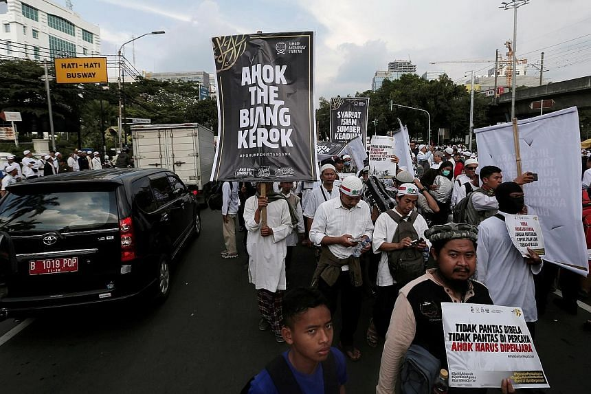 Hardline Muslims protesting in front of the Supreme Court in Jakarta yesterday to call for maximum punishment for Jakarta Governor Basuki Tjahaja Purnama (above), ahead of the verdict of a blasphemy trial next week.