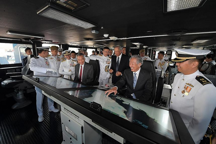 Prime Minister Lee Hsien Loong with Defence Minister Ng Eng Hen and Deputy Prime Minister Teo Chee Hean on the bridge of the RSS Independence at Changi Naval Base yesterday. The warship is the first of eight littoral mission vessels to be commissione