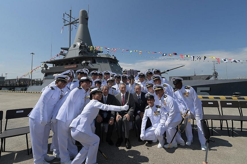 Prime Minister Lee Hsien Loong, flanked by Deputy Prime Minister Teo Chee Hean and Defence Minister Ng Eng Hen, sitting for a wefie with the crew of littoral mission vessel RSS Independence, which can be seen in the background.