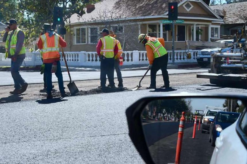 Workers help re-pave a road in South Pasadena, California.