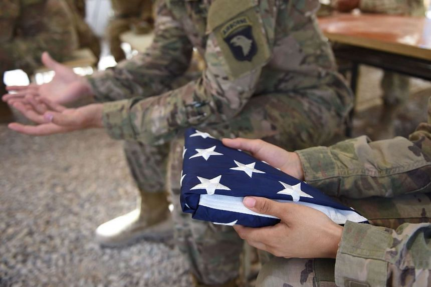 A US soldier holding the national flag.
