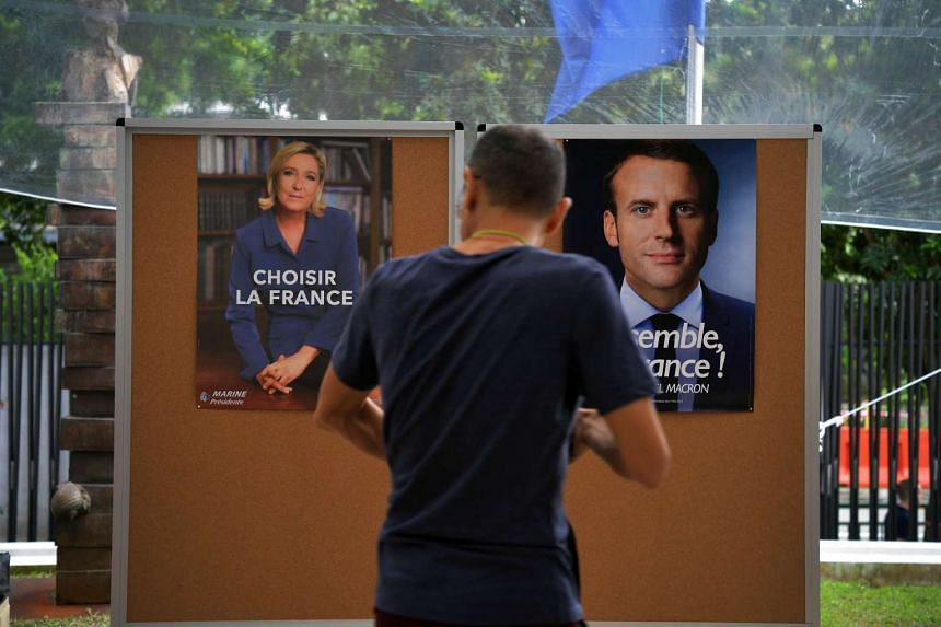 A French voter walking past the campaign posters of Marine Le Pen (left) and Emmanuel Macron at the French Embassy in Singapore, on May 7, 2017.