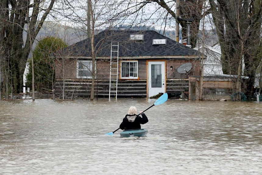 A woman kayaks through a flooded residential area of Rigaud, Canada, on May 6, 2017.