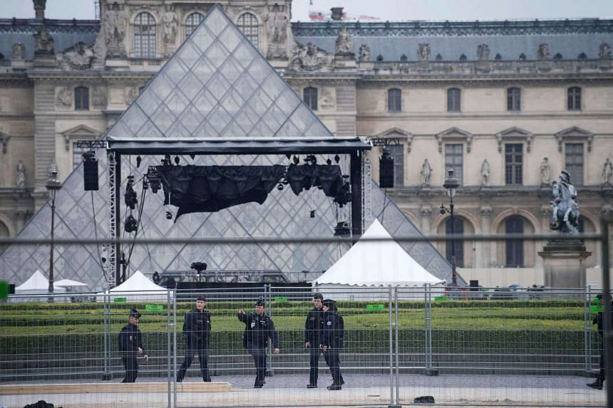 French police officers setting up a security perimeter around the Louvre Pyramid in Paris on May 7, 2017.