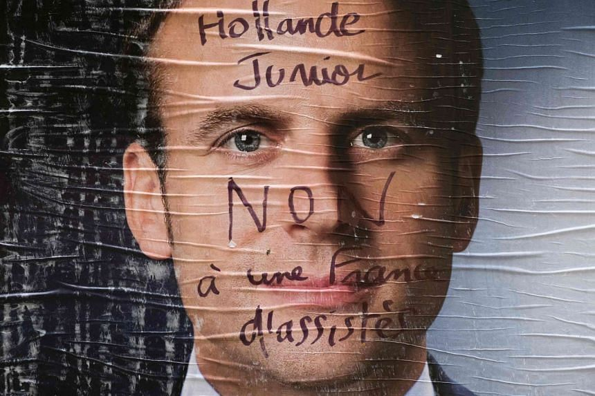 An electoral poster of French presidential election candidate Emmanuel Macron which is covered with a graffiti.