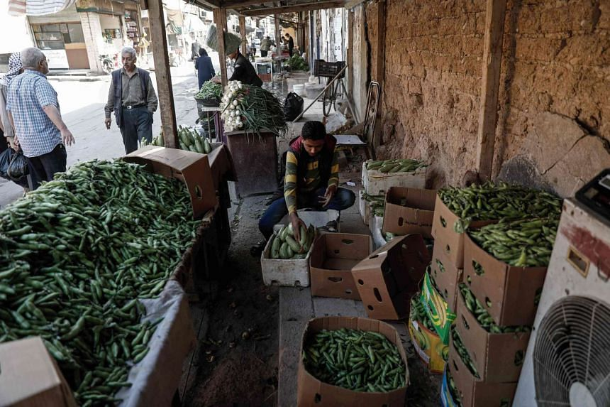 A man sells vegetables in the rebel-held town of Douma, on the eastern outskirts of Damascus, May 6, 2017.
