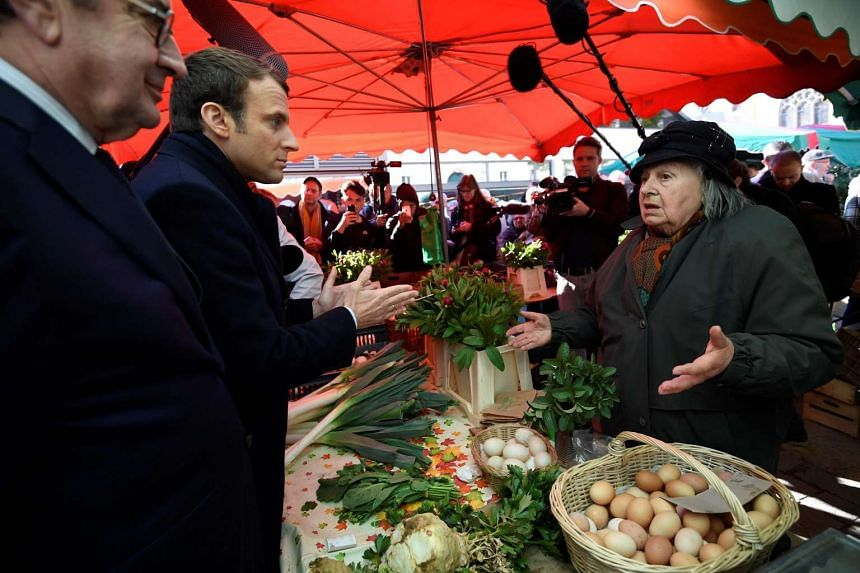 French presidential election candidate Emmanuel Macron (2nd left) campaigning on a market in Poitiers.