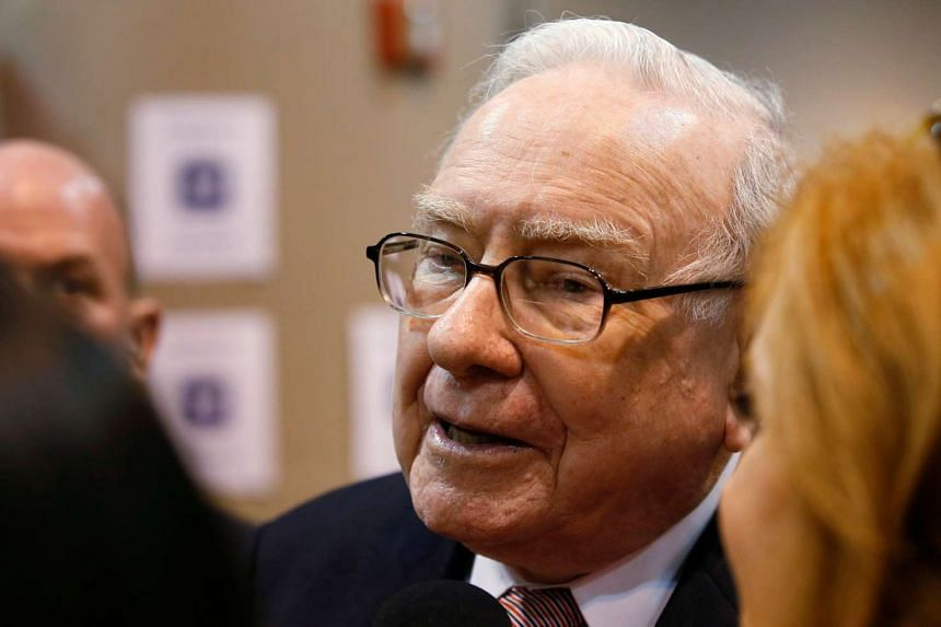 Warren Buffett talks to a reporter before the Berkshire Hathaway annual meeting in Omaha, Nebraska.