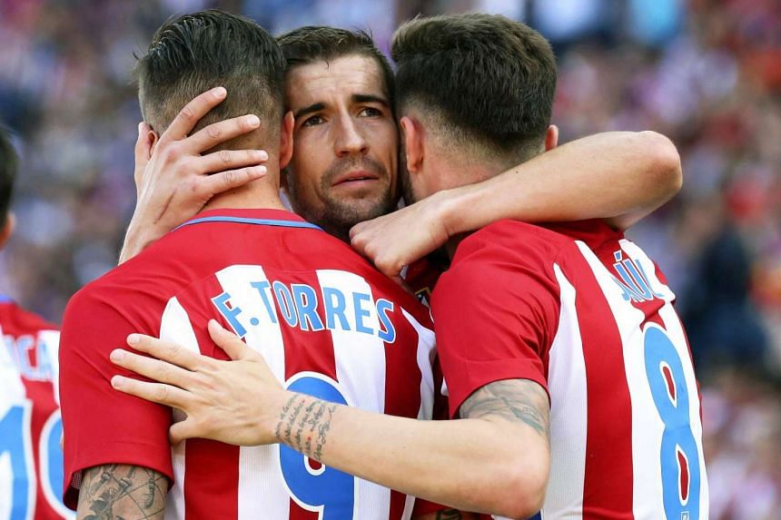 Atletico Madrid's Saul Niguez (right) celebrates with teammates Fernando Torres (left) and Gabi Fernandez.