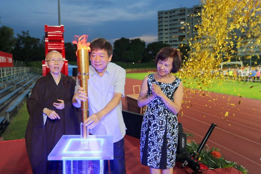 Minister Khaw Boon Wan, flanked by his wife Jean and the Venerable Kuan Yan, lighting up the torch at the pre-Vesak Day event at Hougang Stadium on May 7, 2017.