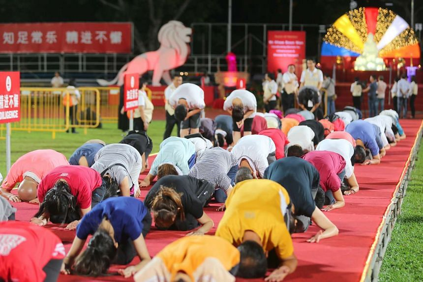 Devotees bowing down during the Peace Homage at Hougang Stadium, on May 7, 2017.
