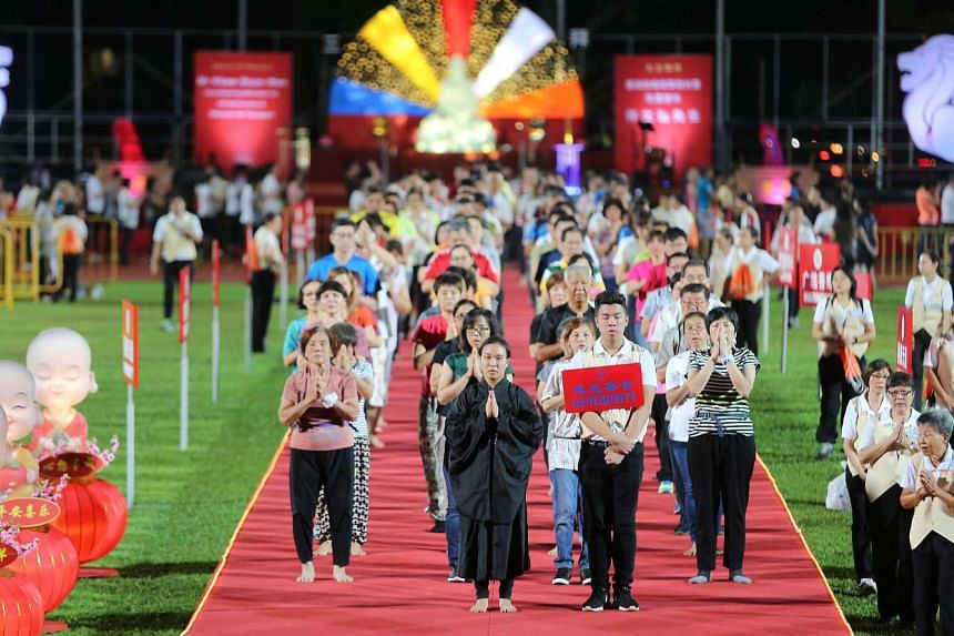 Devotees participating in the three-step-one-bow Peace Homage at Hougang Stadium, on May 7, 2017.