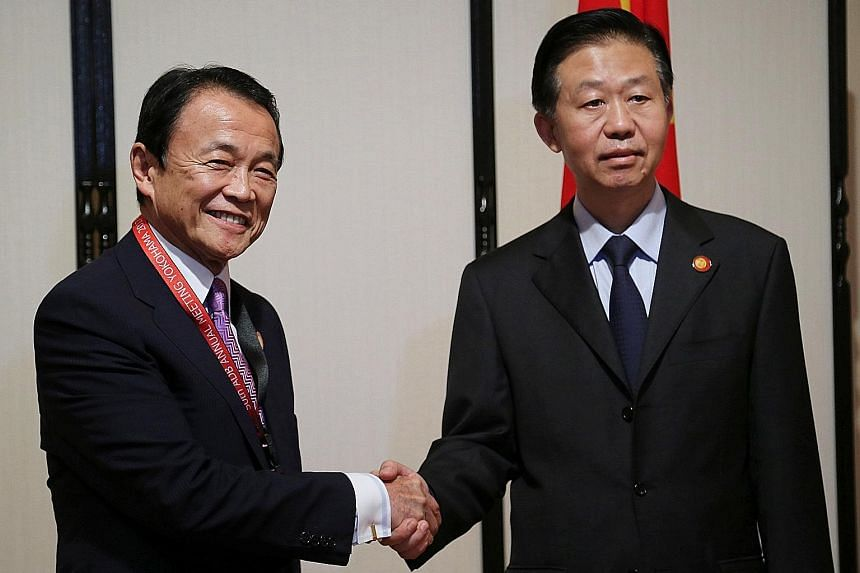 Japanese Finance Minister Taro Aso (left) and his Chinese counterpart Xiao Jie in Yokohama, Japan, yesterday. They did not discuss issues such as geopolitical risks from North Korea's nuclear programme during the dialogue.