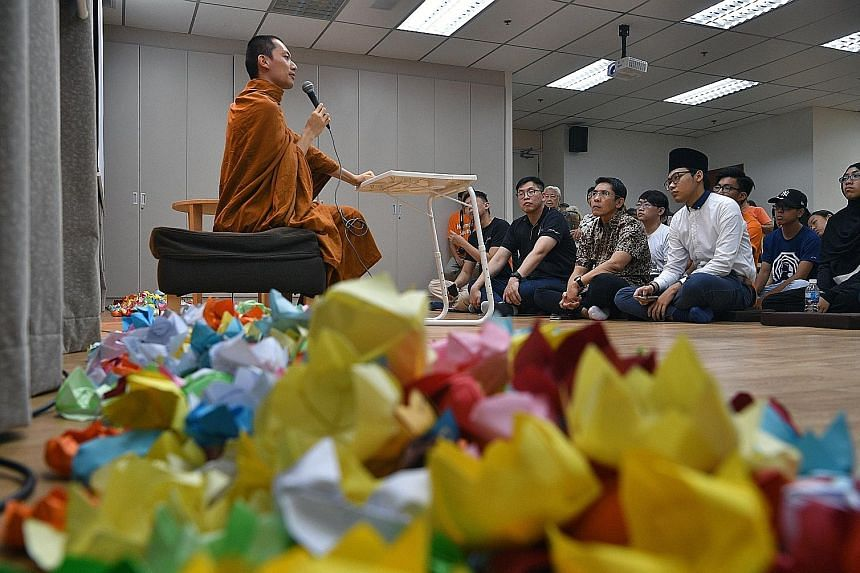 Venerable Phra Chun Kiang speaking at the Buddhist Fellowship East Centre yesterday, surrounded by paper lotus flowers that stand for purity in the Buddhist faith. Listening is South East District Mayor Maliki Osman (first row, second from right), wh